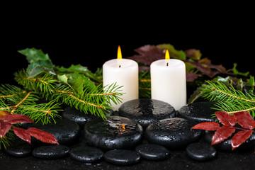 winter spa concept of zen basalt stones, evergreen branches, red