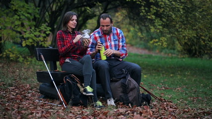 Young couple enjoying a picnic in autumn forest