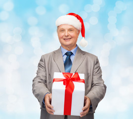 smiling man in suit and santa helper hat with gift