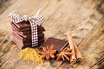 Chocolate, cinnamon and anise beside the wooden table.