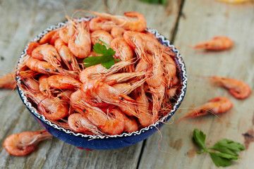 Prepared shrimp on blue plate on wooden background