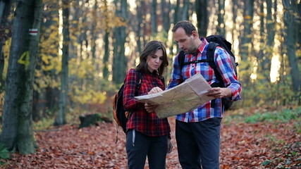 Young couple with a map lost in forest