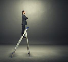 businessman standing on the stepladder