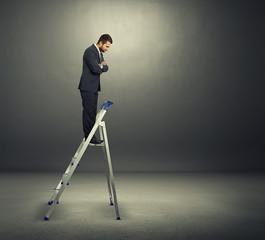 man standing on the stepladder over dark
