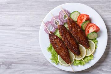 Kebab of minced meat on wooden skewers,  top view
