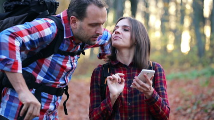 Young couple looking for direction with smartphone in forest