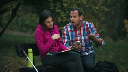 Young couple hikers with tablet and smartphone having quarrel in