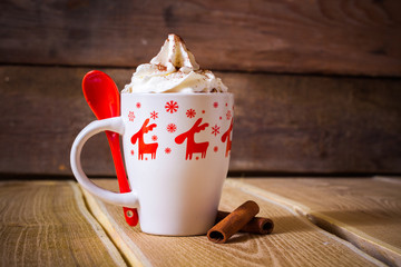 Hot chocolate with whipped cream in a mug with reindeer