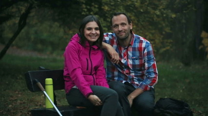 Portrait of happy, smiling couple on the bench in the forest