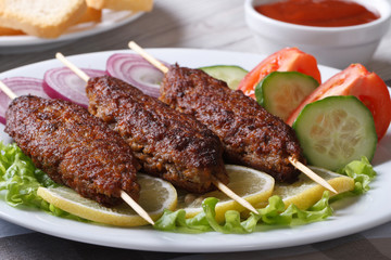 kebabs on wooden skewers and fresh vegetables on a plate