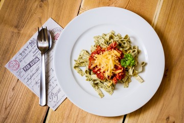 Green herb pasta with bolognese sauce on plate, top view