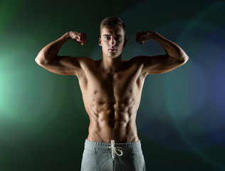 young man showing biceps and muscles