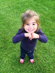 Bambina al parco che gioca, prato verde in background