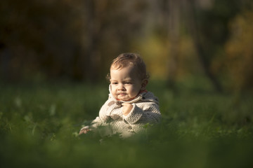 Baby boy sitting among green grass on spring lawn