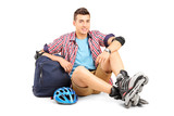 Young man with rollerblades sitting on the floor