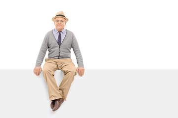 Senior gentleman sitting on a blank billboard