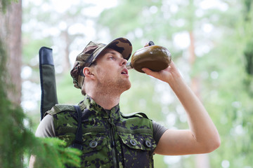 young soldier with gun and flask in forest
