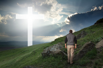 Man in the field walking to the cross