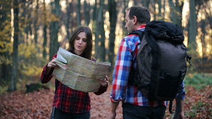 Young woman with map asking for direction in forest