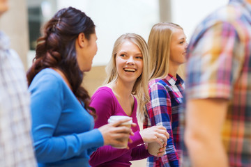 group of smiling students with paper coffee cups