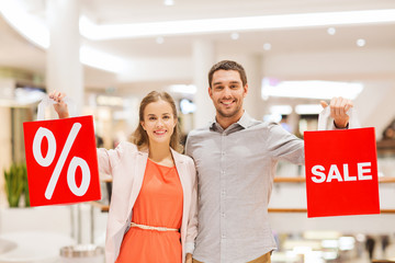 happy young couple with red shopping bags in mall