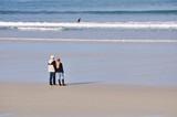 Couple sur une plage face aux vagues et à l
