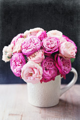 Beautiful fresh roses in a ceramic vase on a table.