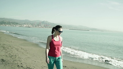 Young, sporty woman walking through the beach