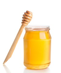 opened honey jar on white background near wooden honey dipper