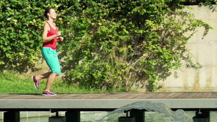 Young, sporty woman jogging in city park