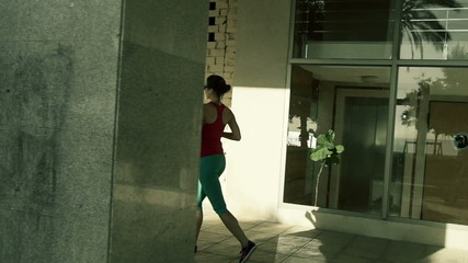 Young, attractive woman jogging in the city during sunny day