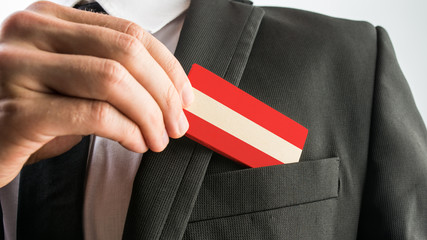 Man withdrawing a wooden card painted as the Austrian flag