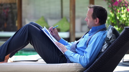 Young businessman signing documents while lying on sunbed