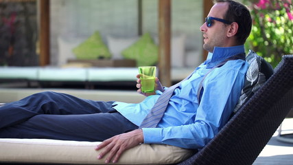Young businessman drinking water and relax on sunbed