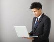 young smiling business man using laptop