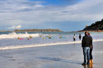 Couple regardant les élèves d'une école de surf sur une plage
