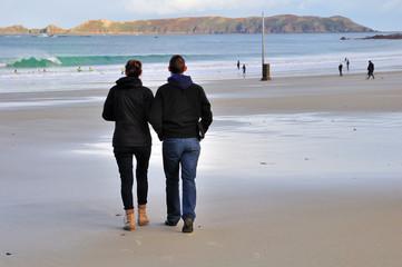 Couple se dirigeant vers la mer sur une plage en Bretagne