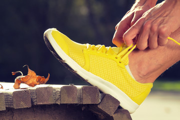 Tying running sneakers on a park bench.