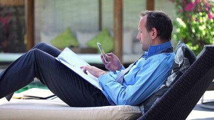 Handsome businessman counting results with smartphone on sunbed