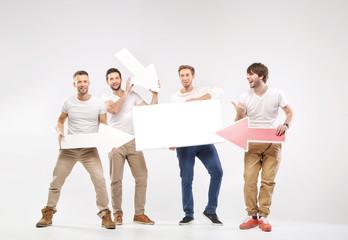 Group of joyful guys holding symbols