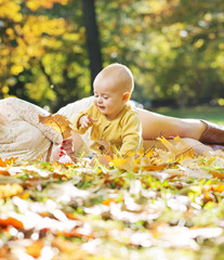 Little child playing autumn leaves