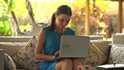 Young,beautiful woman sitting with laptop on sofa at home
