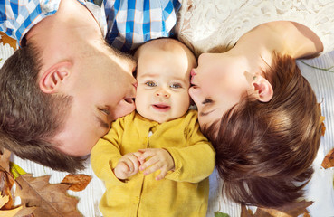 Young parents kissing their child