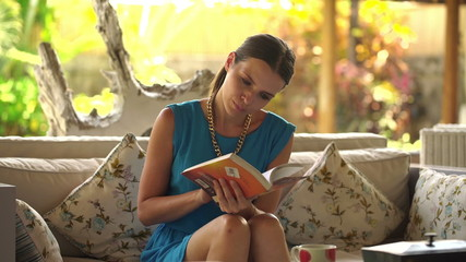 Young,beautiful woman reading book on sofa at home