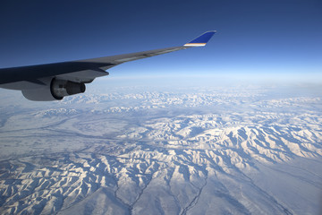 Flying over Siberia mountains covered with snow