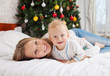 Happy mother and baby son on bed at Christmas time