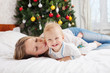 Happy mother and baby boy on bed at Christmas time
