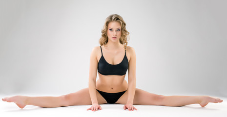 Charming young woman doing gymnastic splits
