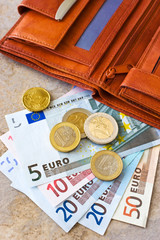 Euro money - banknotes and coins - in brown wallet