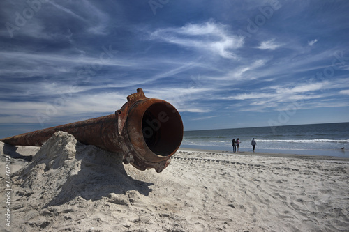 Leinwandbild Motiv rusty pipes along the sea beach